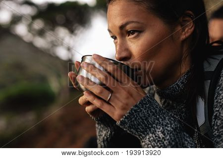 Close up shot of young asian woman drinking coffee taking break during hiking. Female hiker taking rest on mountain hill.