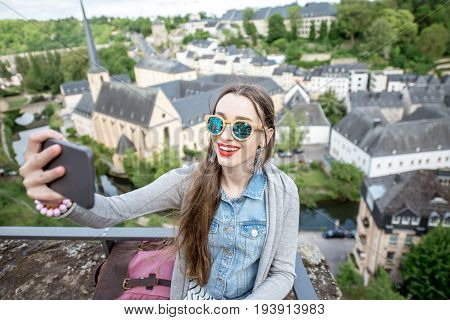 Young female traveler making selfie photo on the old town background in Luxembourg city