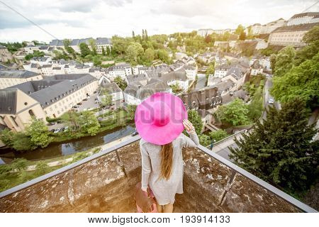 Female traveler standing back with pink hat and enjoy beautiful cityscape view on the old town in Luxembourg city