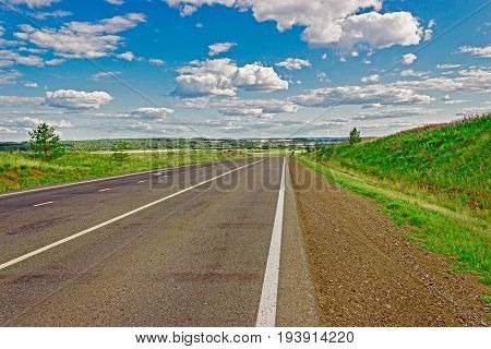View of the road in the wooded hills on a summer day