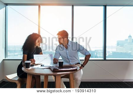 Young man and woman discussing work over a cup of coffee sitting in office. Businesswoman holding a paper in hand while taking to her business colleague.