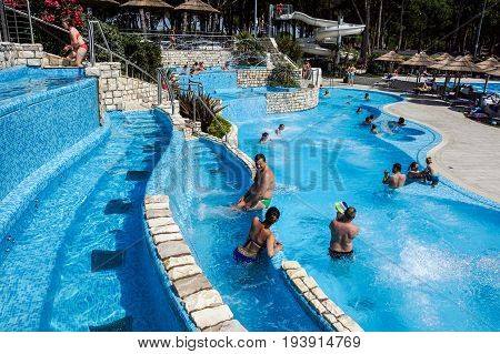 Torvaianica, Italy - July 2017: People having fun in the swimming pool in water park at Zoomarine acqua park .
