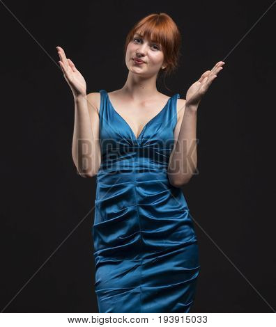 Young enigmatic woman showing by hands on a black background. Ideal for banners, registration forms, presentation, landings, presenting concept.