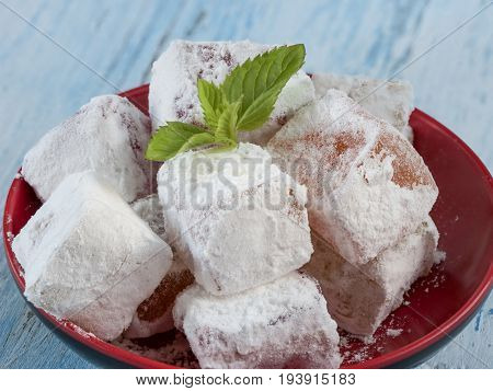 Turkish delights in plate on vintage table. Sweet Turkish delight lokum traditional dessert.