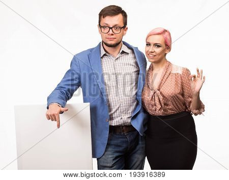Young confident couple portrait of a confident businessman showing presentation, pointing paper placard background. Ideal for banners, registration forms, presentation, landings, presenting concept.