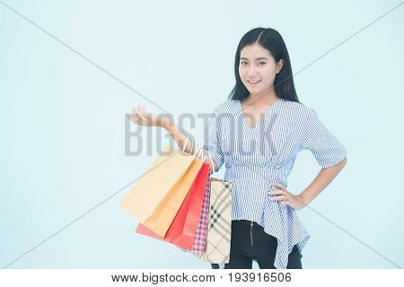 Woman holding with shoping bag and posing isolated on blue background