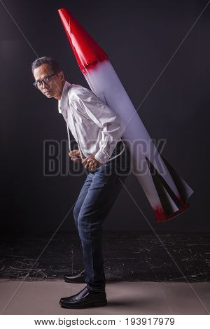 asian man carrying red head missile on back