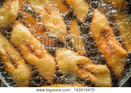 Frying Delicious And Traditionally Donuts On Hot Oil
