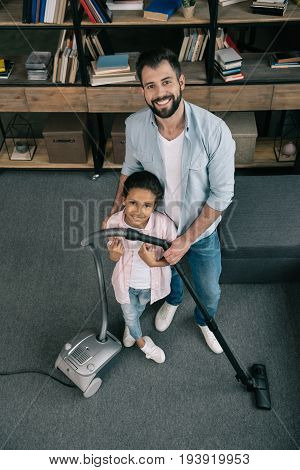 smiling father and daughter tidying up with vacuum cleaner and looking at camera at home