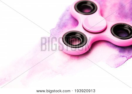 Pink plastic beautiful spinner on watercolor background with splashes. Isolated on white background.