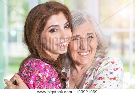 Portrait of a young beautiful woman hugging her mother
