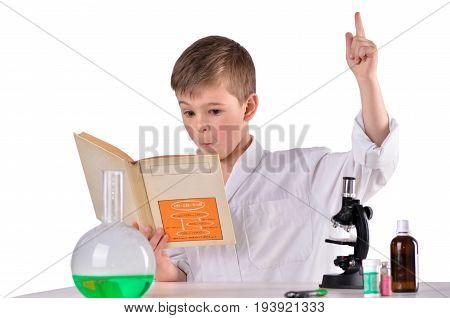 Surprised scientist boy in whie robe find solution in his book