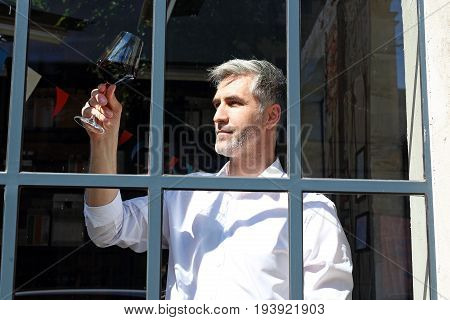 Young wine Man admires the color of wine in a glass.