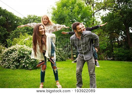 Happy joyful family in a summer park have fun playing imitation flight