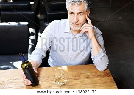 White or red wine? Man pours wine into a glass.