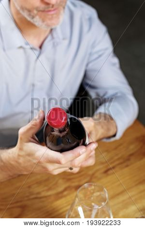 Wine selection. Man reading a label on a bottle