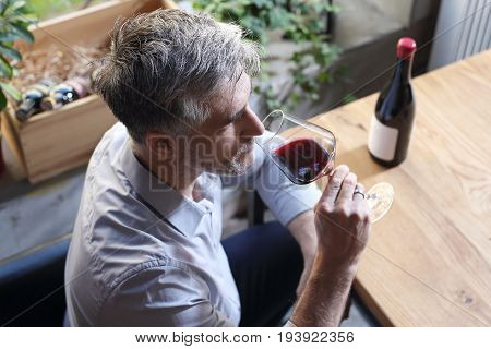 Man drinking wine. A glass of red wine. Handsome man drinking wine.