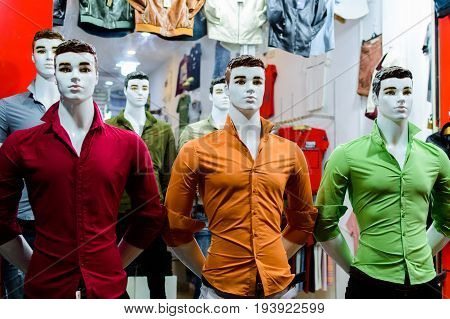 Men's clothing store. Mannequins dressed in colored shirts in clothing store.