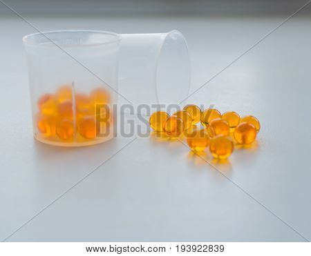 Fish Oil Capsules In Measuring Cup On White Medical Table