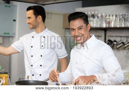 Mature chef in kitchen cooking dish for dinner with smile 30-40 year old.