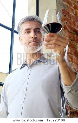 A glass of red wine. Handsome man drinking wine.