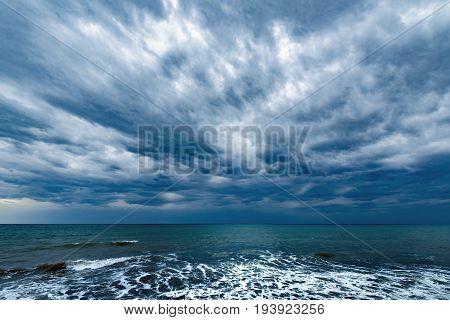 Dark stormy sky above the ocean surface.