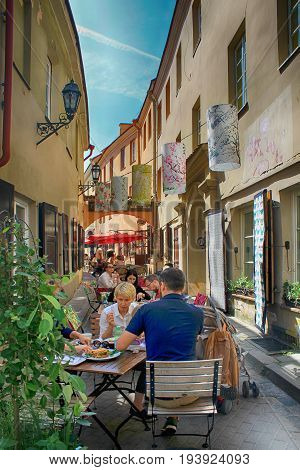 VILNIUS, LITHUANIA - JULY 18, 2015: People eat and drink at sidewalk cafe in the historic Old Town of Vilnius, Lithuania, Eastern Europe.