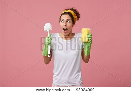 Surprised Housewife In Casual White T-shirt And Ptotective Gloves For Cleaning Going To Tidy Up Room
