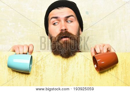 Bearded man long beard. Brutal caucasian surprised unshaven hipster in black hat with yellow paper sheet holding colorful cups on texture studio background