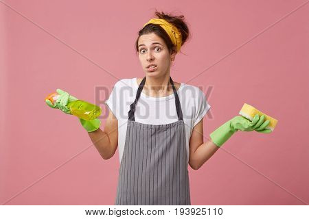 Attractive Female With European Appearance Wearing Apron Shrugging Her Shoulders In Perplexity While