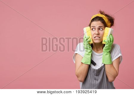 Waist Up Shot Of Beautiful Young Housewife Looking Sideways With Scared Terrified Expression, Holdin