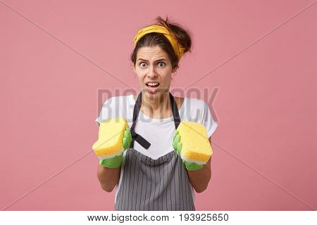 Portrait Of Spoiled Young Woman Wearing Headband, Apron And Green Rubber Gloves Feeling Frustrated A