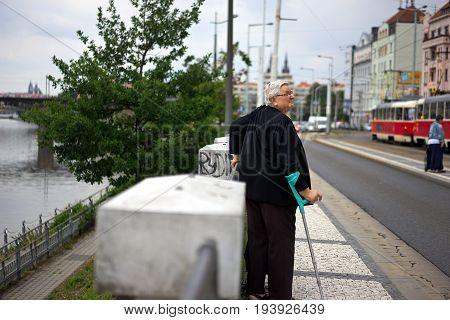 Prague Czech Republic-4 July 2017: An elderly lady with a crutch awaiting a tram