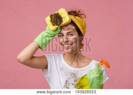 Portrait Of Beautiful Young Housewife With Dirty Clothes And Face Holding Mop And Washing Spray Hold
