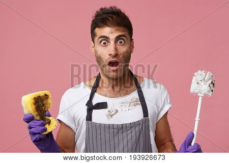 Astonished Man With Bugged Eyes And Opened Mouth Having Trendy Hairstyle Wearing Apron And Brush Bei