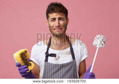 Studio Shot Of Stressed Sad Handsome Student Standing At Pink Wall With Toilet Brush And Sponge Whin