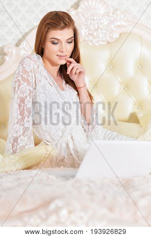 Beautiful young woman on bed with laptop