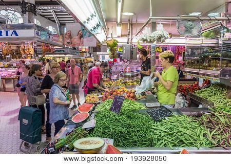 VALENCIA, SPAIN - JUNE 12, 2017: Vegetable stall with people at the Mercado Central of Valencia, Spain