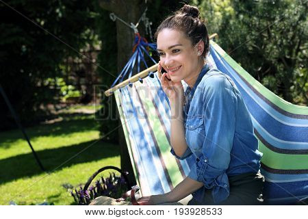 Spring break on the hammock. Young attractive woman relaxing on a hammock in the garden talking on the phone.