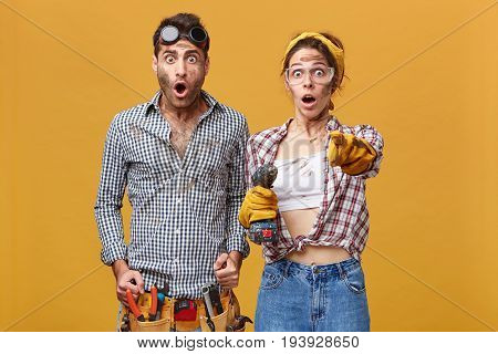 Surprised Couple Of Male And Female Electical Technicians In Protective Goggles And Overalls Having