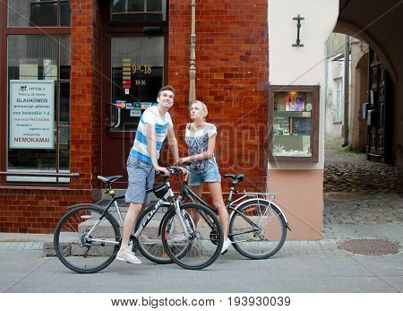 VILNIUS, LITHUANIA - JULY 18, 2015: Couple walking with bicycle on Old Town street, Vilnius, Lithuania.