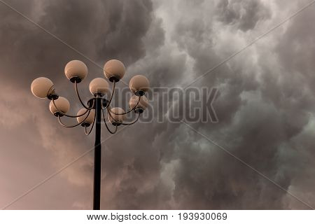 Lightning flashes stormy clouds over big glorious street lamp