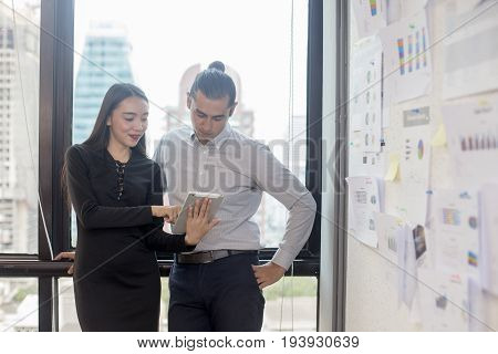 businesspeople using tablet and working together at workplace 20-30 year old.