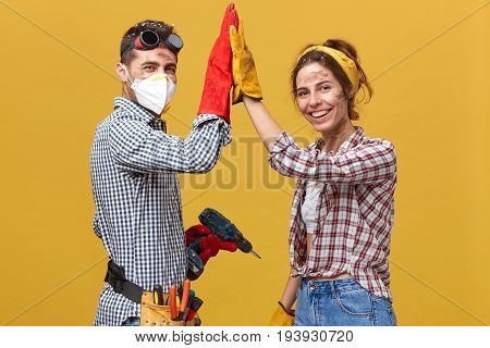 People, Occupation, Teamwork, Cooperation Cocncept. Caucasian Couple Standing Sideways Doing Constru