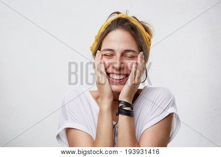 Positive Cheerful Female Holding Her Hands On Cheeks Smiling Broadly Closing Her Eyes With Pleasure