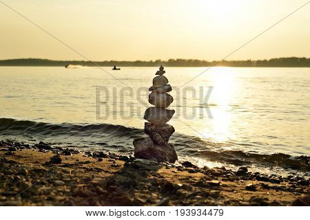 Balanced rock cairn built by tourists on the shore of the most majestic rivers of Russia. Photographed at sunset. Samara Russia August 4 2016