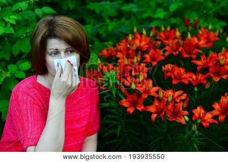 A woman with an allergic rhinitis near lilies in nature