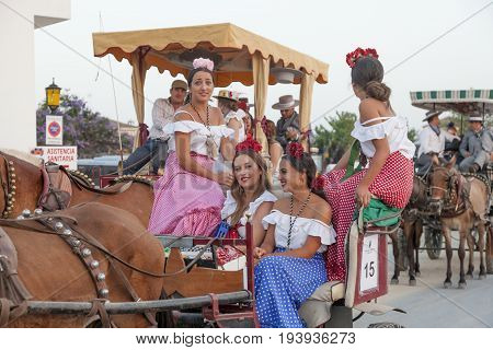 El Rocio Spain - June 1 2017: Group of female pilgrims in traditional spanish flamenco dress on the road to El Rocio during the Romeria 2017. Province of Huelva Almonte Andalusia Spain