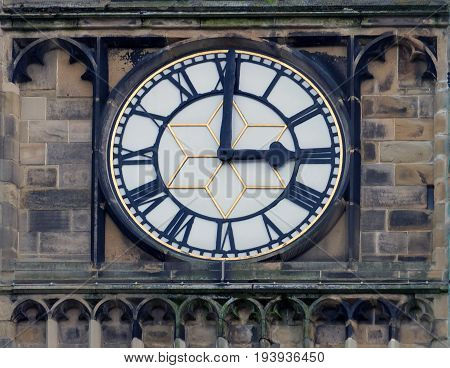 church clock white face with roman numerals at three o clock in the church in huddersfield