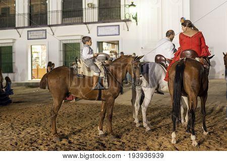El Rocio Spain - June 1 2017: Group of pilgrims on horseback in traditional spanish dress in El Rocio during the Romeria 2017. Province of Huelva Almonte Andalusia Spain